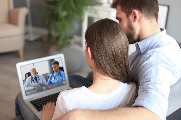 Giovani coppie che fanno videoconferenza con i medici sul computer portatile. coronavirus.