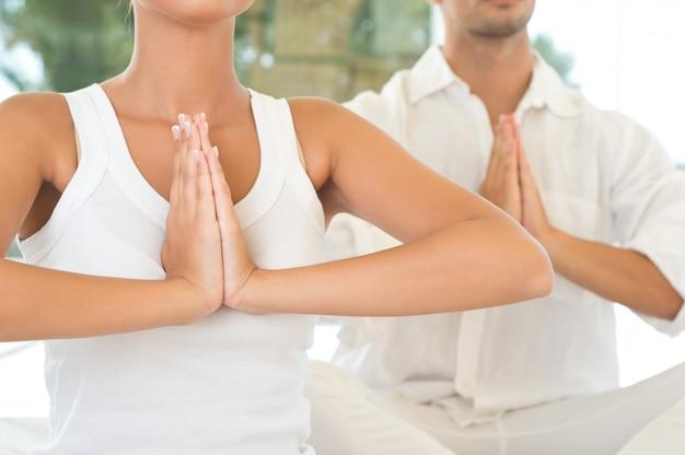 Giovane coppia facendo yoga e meditazione, colpo del primo piano