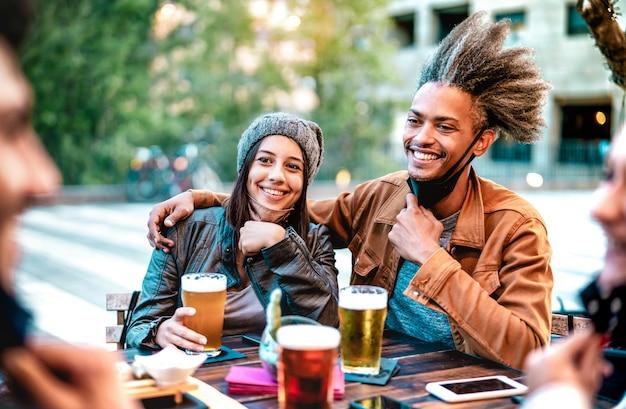 Giovani coppie che bevono bicchieri di birra che indossano maschere facciali aperte con focus sulla donna