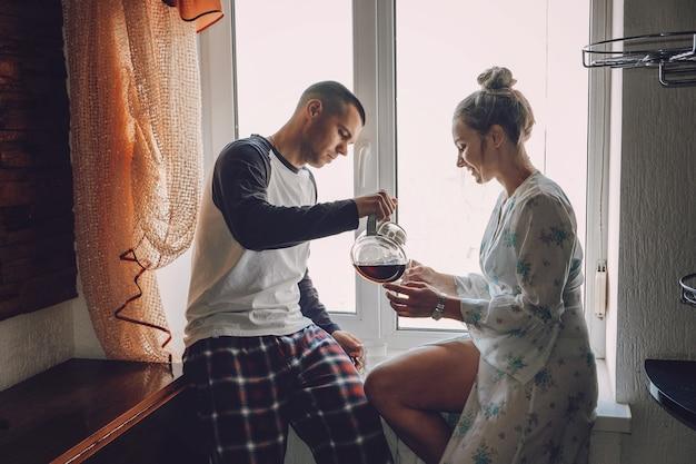 Giovane coppia che beve caffè in cucina a casa la mattina giovane coppia felice sposini famiglia