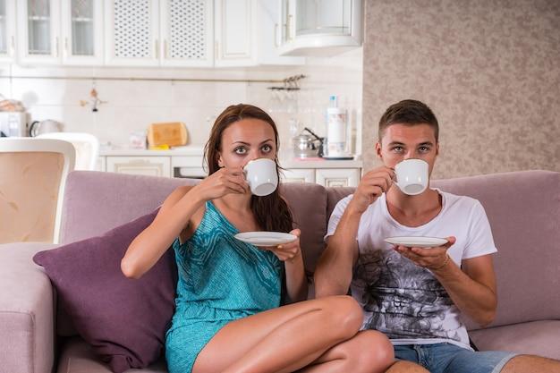 Giovane coppia che beve caffè o tè dalle tazze mentre è seduta fianco a fianco sul divano e guarda nella stessa direzione in una piccola casa