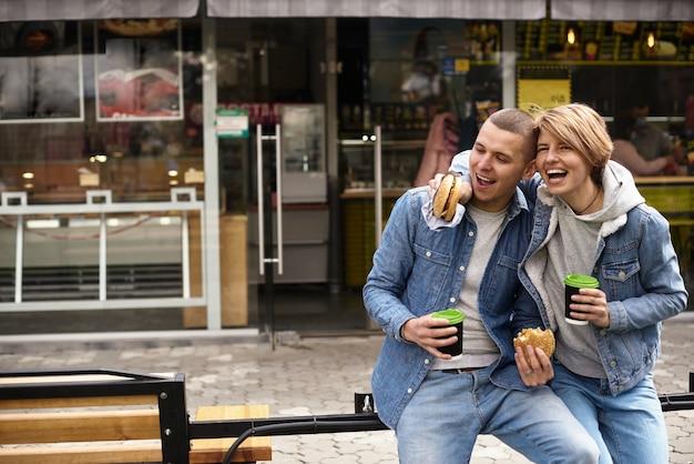Giovani coppie che bevono caffè mentre si cammina per la città