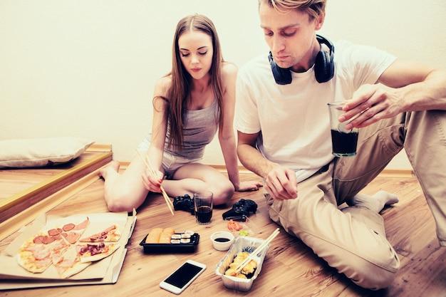 Le giovani coppie mangiano insieme sushi a casa. riprese in interni.