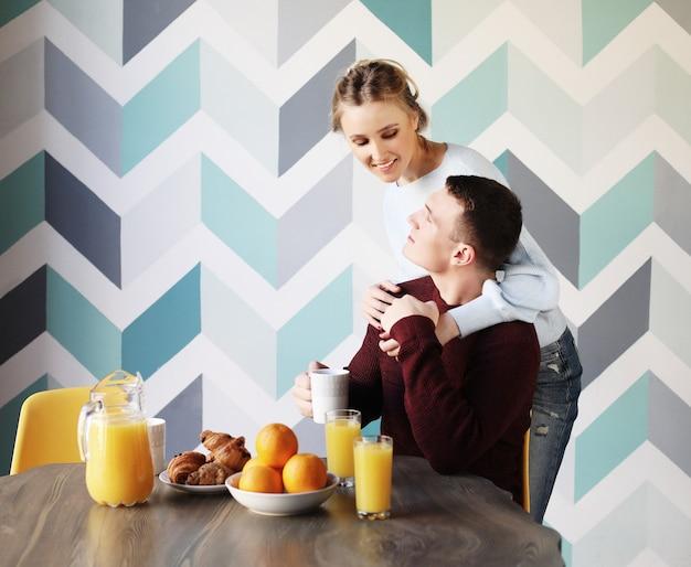 Giovane coppia fare colazione la mattina presto in cucina e divertirsi.