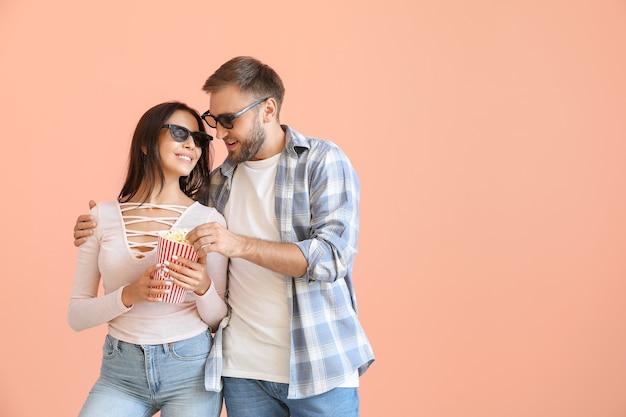Giovani coppie che mangiano popcorn sul colore di sfondo