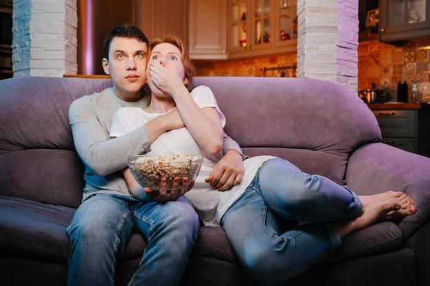 Giovane coppia che mangia popcorn e guarda un film a casa sul divano molto spaventata