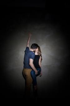 Giovani coppie che si abbracciano e si baciano sullo sfondo grigio scuro