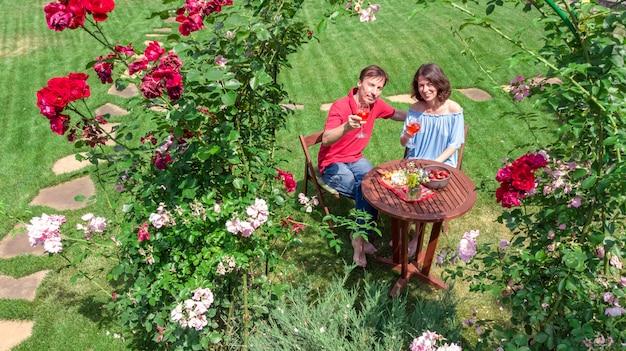 Giovani coppie che godono dell'alimento e del vino nel bello giardino di rose alla data romantica