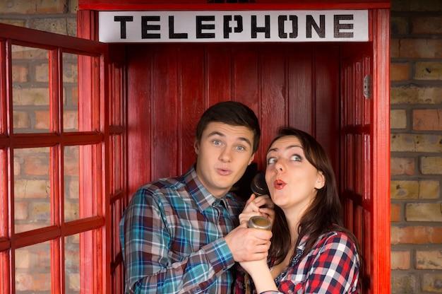 Giovane coppia che si gode un pettegolezzo mentre stanno vicini in una cabina telefonica condividendo il ricevitore e ansimando in gioiosa attesa per una succosa notizia