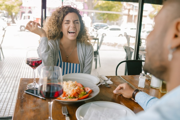 Coppia giovane godendo e pranzando insieme durante un appuntamento in un ristorante.