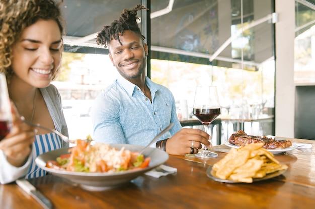 Giovani coppie che si divertono e trascorrono del tempo mentre pranzano insieme in un ristorante. concetto di relazione.