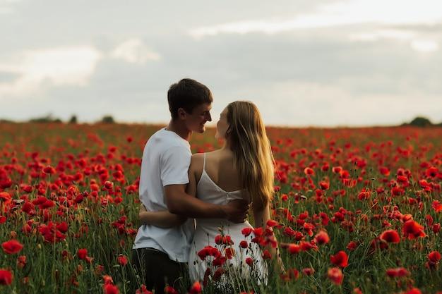 Giovani coppie che si godono il tempo insieme nel prato rosso