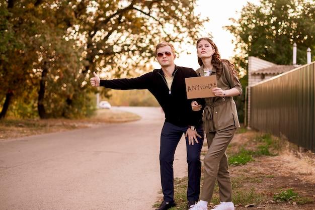 Una giovane coppia famiglia di autostoppisti in autostrada in attesa dell'auto, viaggia in libertà con amore