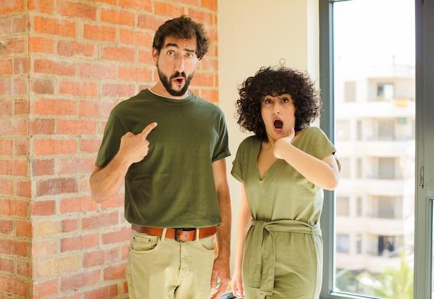 Giovane coppia che si sente triste, arrabbiata o arrabbiata e guarda di lato con un atteggiamento negativo, accigliata in disaccordo