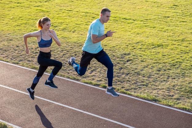 Giovani coppie degli sportivi adatti ragazzo e ragazza che corrono mentre facendo esercizio sulle piste rosse dello stadio pubblico all'aperto.