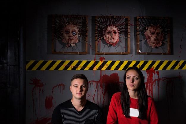 Giovane coppia di fronte a facce scuoiate per la spaventosa scena del crimine del terrore a tema halloween