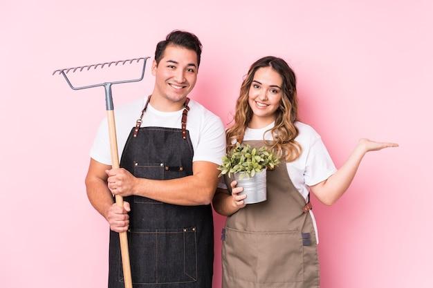 Giardiniere delle giovani coppie che mostra uno spazio della copia su una palma e che tiene un'altra mano sulla vita.