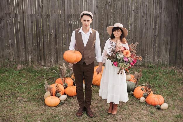 Una giovane coppia si tiene delicatamente per mano. un uomo sta con una zucca in mano e una ragazza con un bouquet.