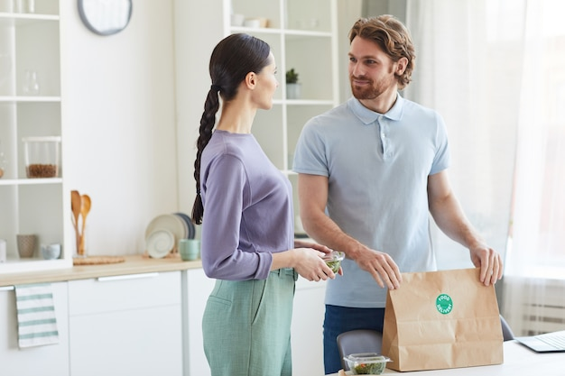 Giovani coppie che ottengono la consegna del cibo che stanno in cucina e parlano tra loro