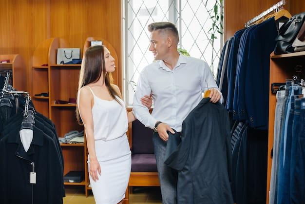 Una giovane coppia va a fare shopping e prende un abito da uomo.