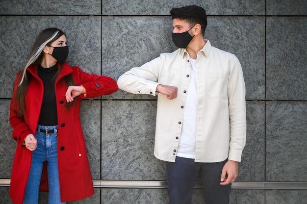 Giovani coppie che salutano con i gomiti all'aperto - concetto di pandemia covid