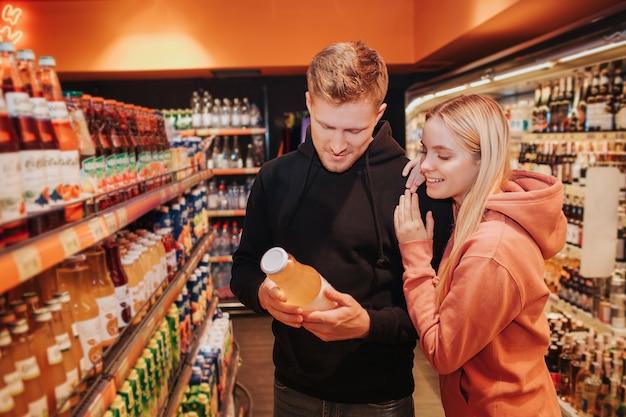 Giovani coppie in drogheria. guardano insieme la bottiglia di succo nelle mani dell'uomo. la giovane donna si appoggia alla spalla del ragazzo.