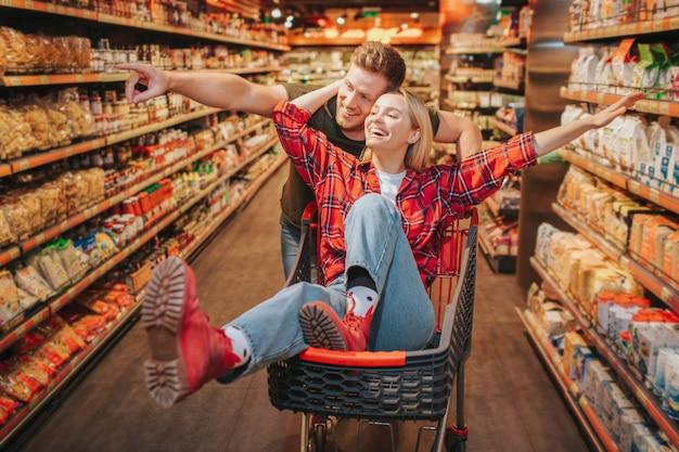 Giovani coppie in drogheria. la donna si siede in carrello e si diverte. l'uomo sta dietro e punta sullo scaffale con i prodotti. coppia felice divertirsi.