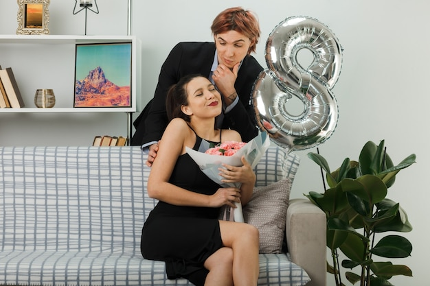 Giovane coppia in una felice giornata delle donne pensando ha afferrato il mento ragazzo in piedi dietro il divano ragazza contenta seduta sul divano con in mano un mazzo di fiori nel soggiorno