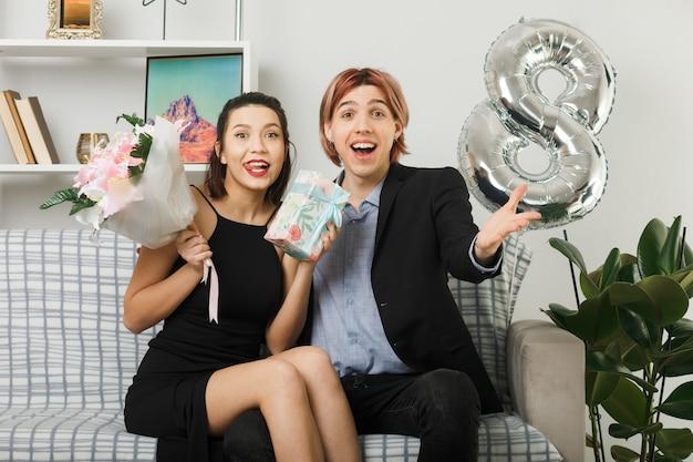 Giovane coppia in felice giornata della donna con bouquet e regalo seduti sul divano in soggiorno