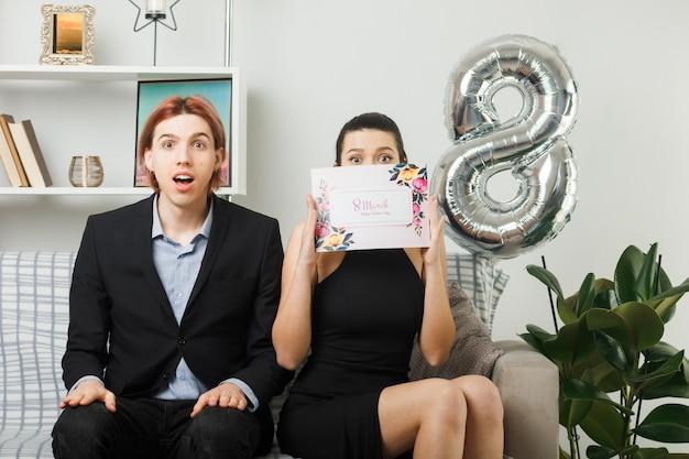 Coppia giovane il giorno della donna felice donna che tiene e faccia coperta con una cartolina seduta sul divano in soggiorno