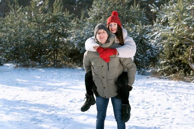 La giovane coppia si diverte nella foresta invernale. guy fa rotolare la ragazza sulla schiena.