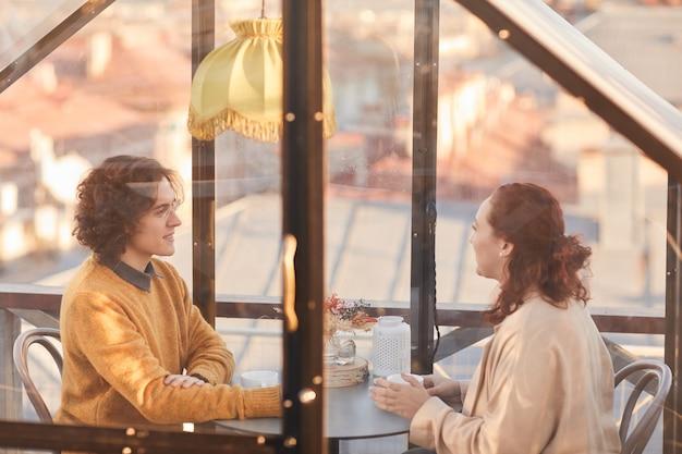 La giovane coppia ha un appuntamento romantico in un caffè che si siedono dietro la finestra bevendo tè e parlando tra loro