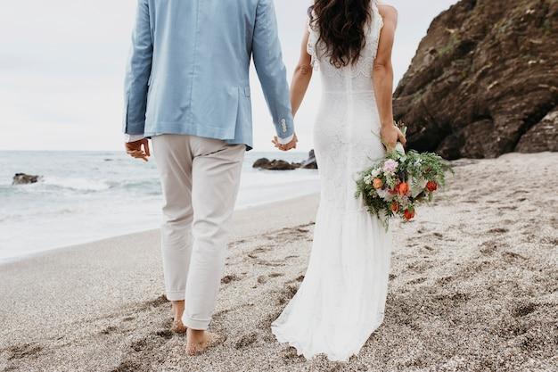 Giovane coppia che ha un matrimonio sulla spiaggia