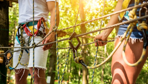 Giovani coppie che hanno tempo di divertimento nel parco avventura avventura. attrezzatura da arrampicata. indossare cinture di sicurezza e caschi protettivi.