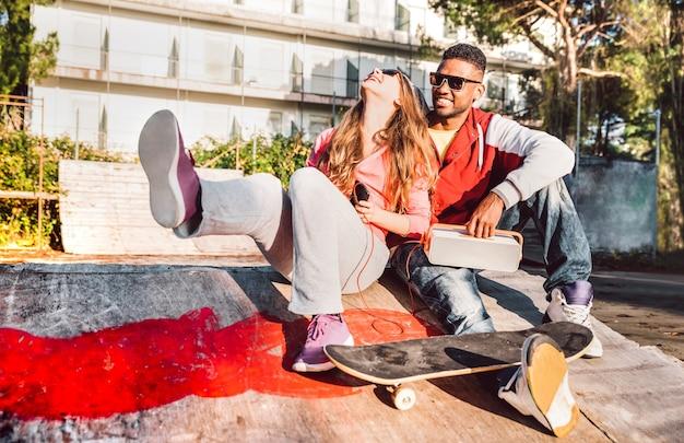 Giovani coppie che hanno divertimento insieme allo skate park con musica boombox