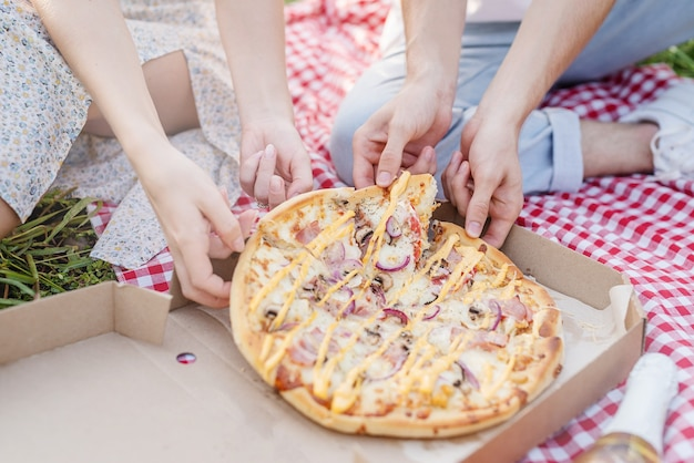 Giovane coppia che fa un picnic mangiando pizza