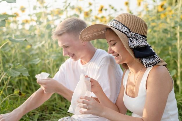 Giovane coppia che fa un picnic sul campo di girasoli al tramonto, asciugandosi le mani e il viso