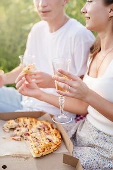 Giovane coppia che fa un picnic sul campo di girasoli al tramonto