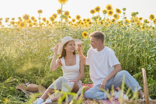 Giovane coppia che fa un picnic sul campo di girasoli