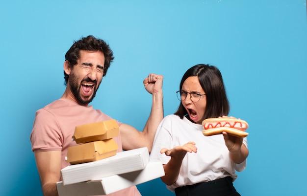 Giovani coppie che hanno take away fast food a casa.