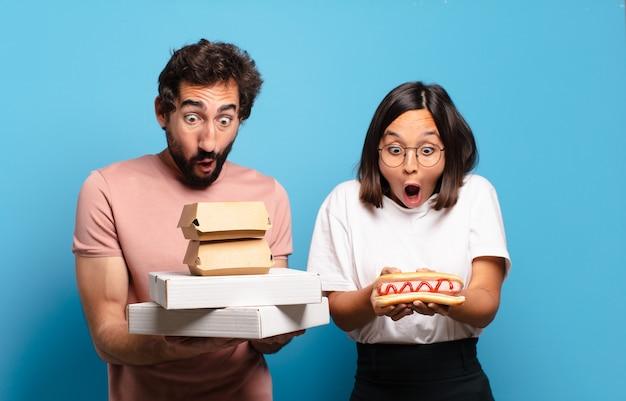 Giovane coppia che mangia fast food da asporto a casa