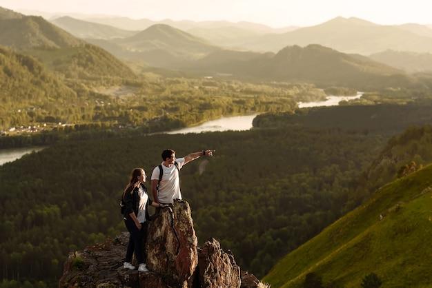Giovane coppia di escursionisti uomo e donna con zaini sulla cima della montagna in riva al fiume