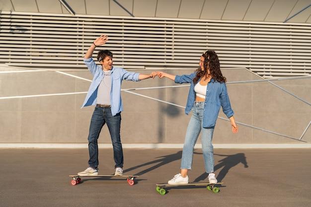 Giovane coppia di skateboarder hipster skate nella città estiva allegro casual ragazzo e ragazza su longboard