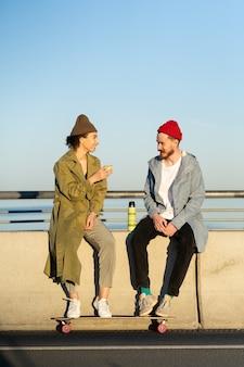 La giovane coppia di skateboarder hipster si rilassa dopo l'allenamento di skateboard seduto sul ponte di cemento concrete