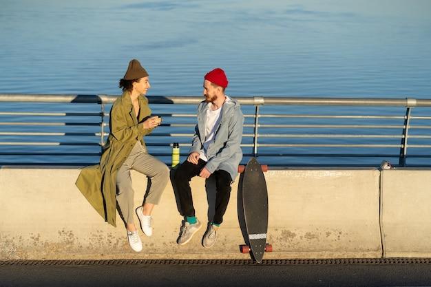 Una giovane coppia di hipster si diverte insieme a sedersi sul ponte del fiume bevendo tè caldo da thermos talk