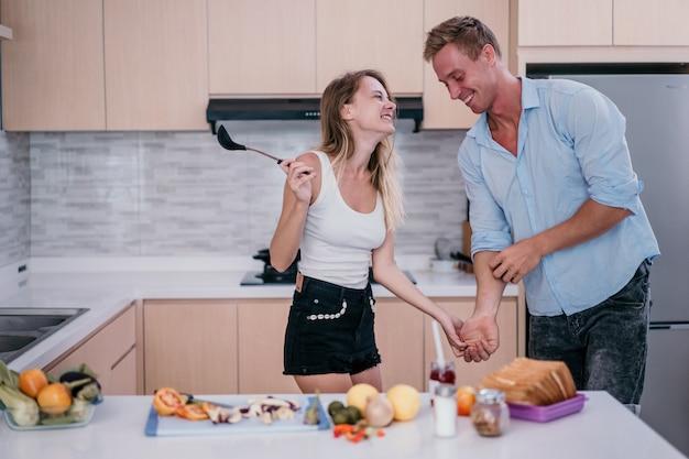 Le giovani coppie si tengono per mano e iniziano a ballare quando si preparano per cucinare