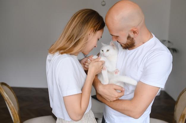 Le giovani coppie tengono un gatto bianco fra le loro braccia