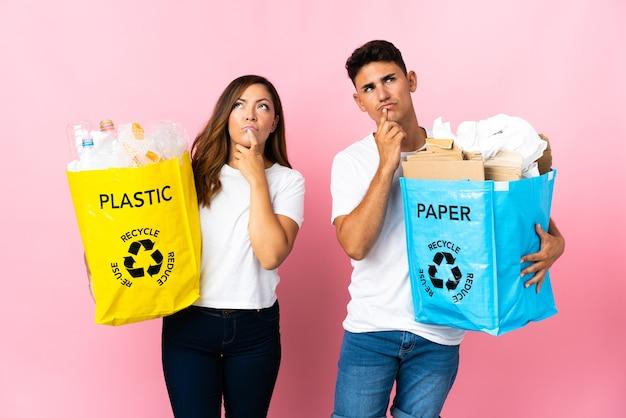 Giovani coppie che tengono un sacchetto pieno di plastica e carta sul colore rosa che hanno dubbi mentre osservano
