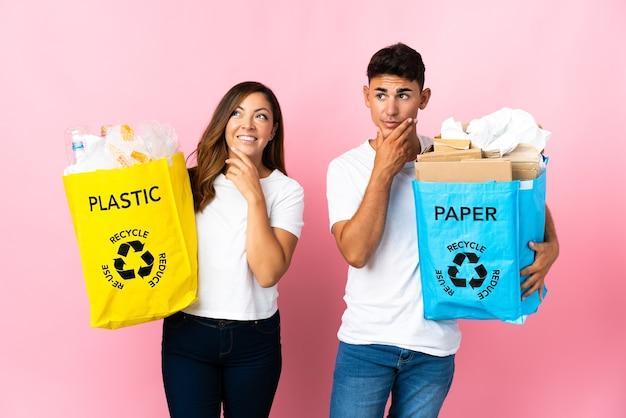Giovani coppie che tengono un sacchetto pieno di plastica e carta sul rosa che osserva in su mentre sorride