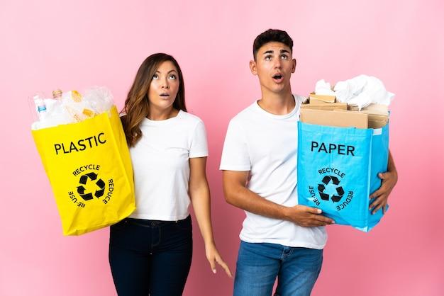 Giovani coppie che tengono un sacchetto pieno di plastica e carta sul rosa che osserva in su e con l'espressione sorpresa
